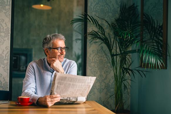 新聞を読む高齢者の写真