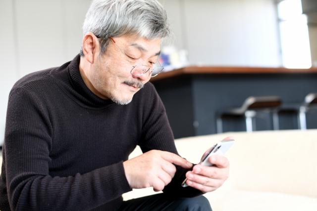 スマホで高齢者向け脳トレアプリを行う中高年の男性