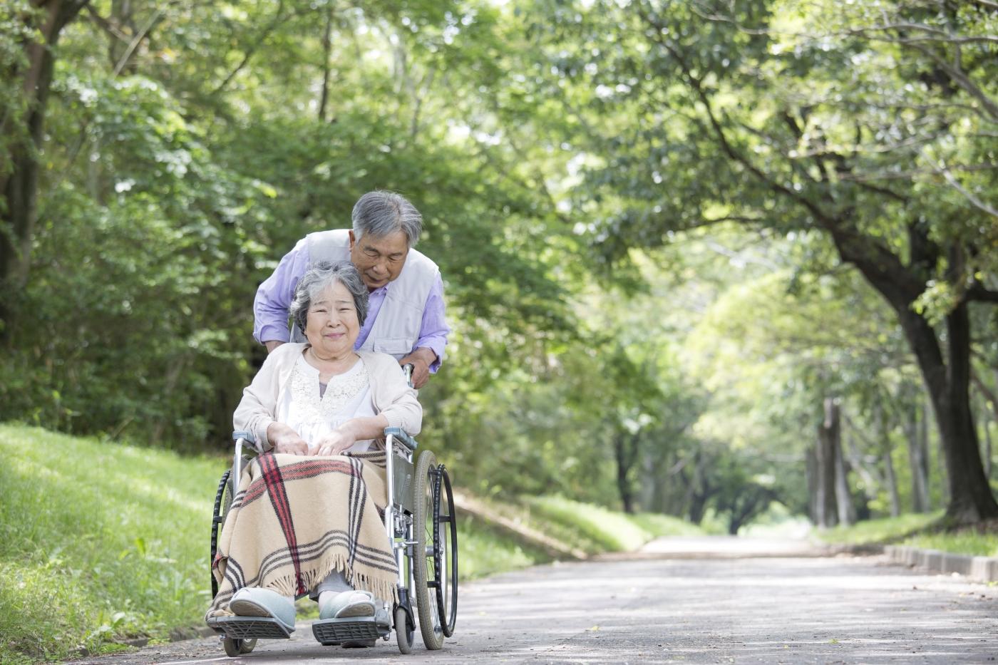 車椅子に乗った高齢女性と車椅子を押す高齢男性の写真
