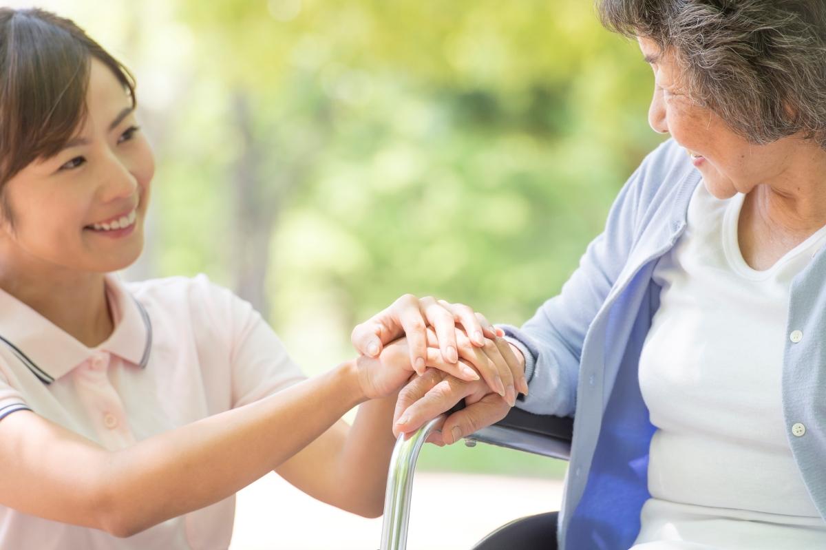 介護スタッフが高齢女性に手を携える写真