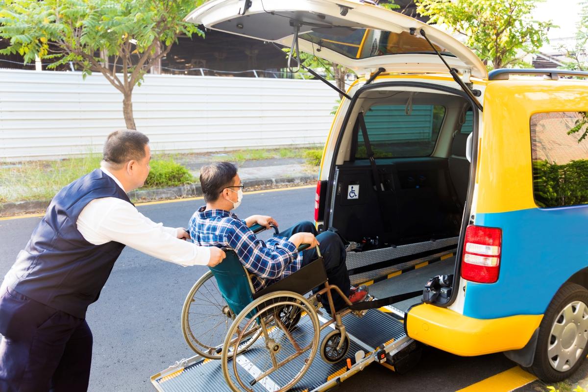 介護タクシーに乗車する車いすに乗った男性の写真