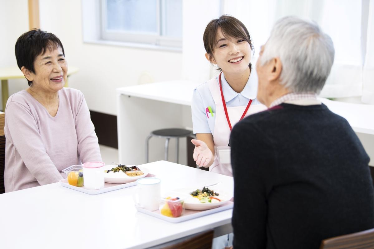 笑顔で食事を楽しむ高齢者と介護スタッフの写真