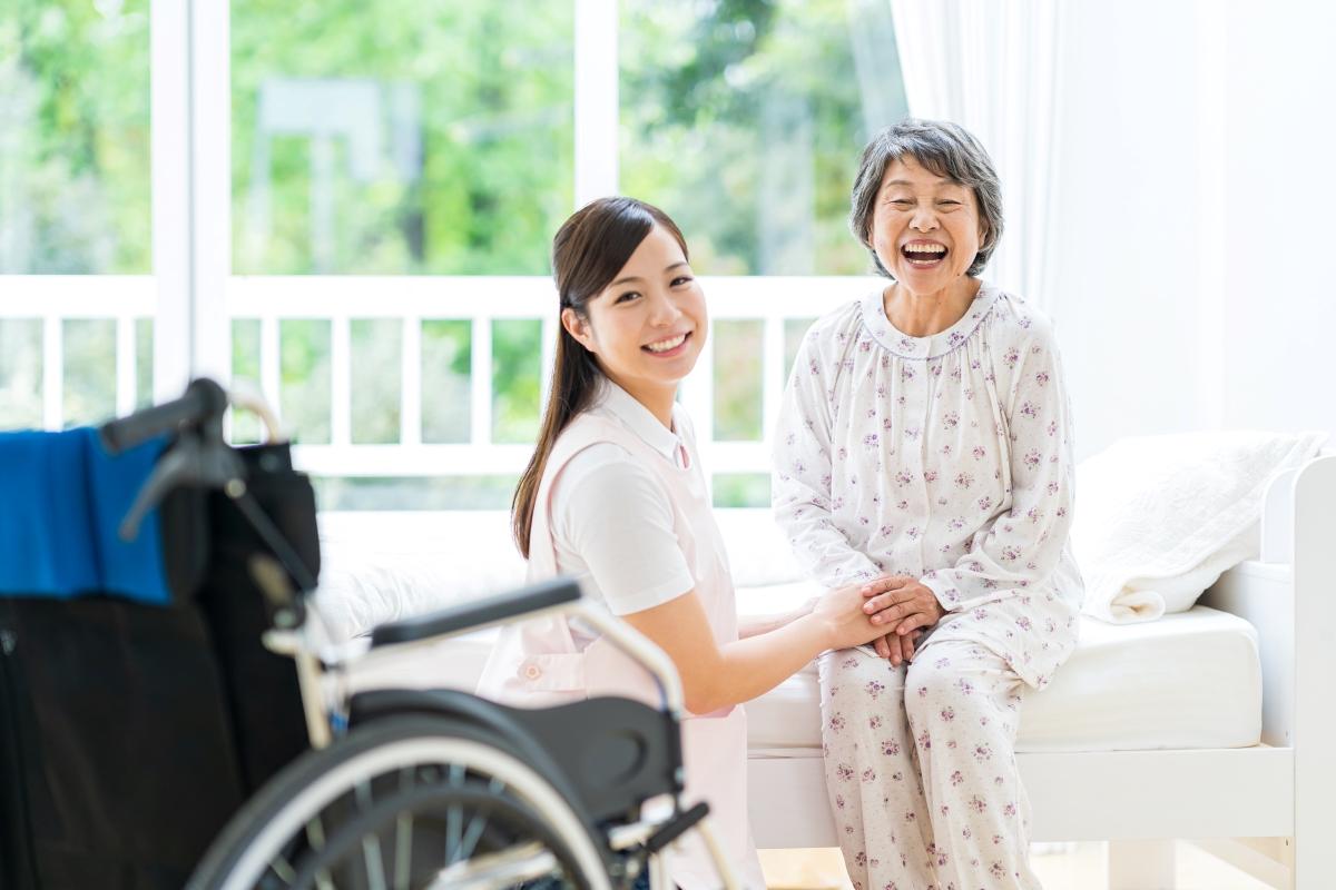 老人ホームの居室で手を取り合う高齢女性と介護スタッフの写真