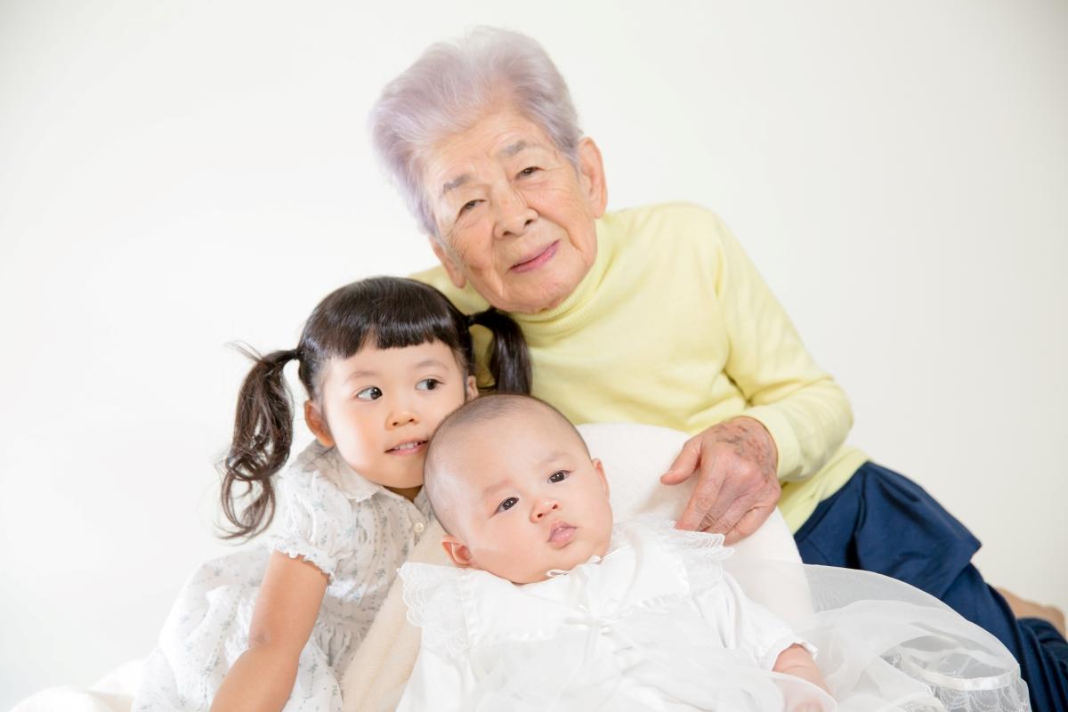 高齢女性と乳児、幼児の写真