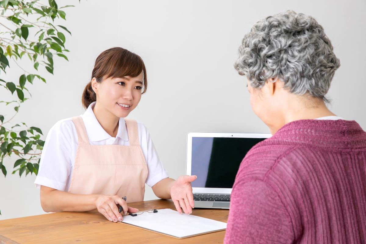 介護スタッフと説明を受ける高齢女性の写真