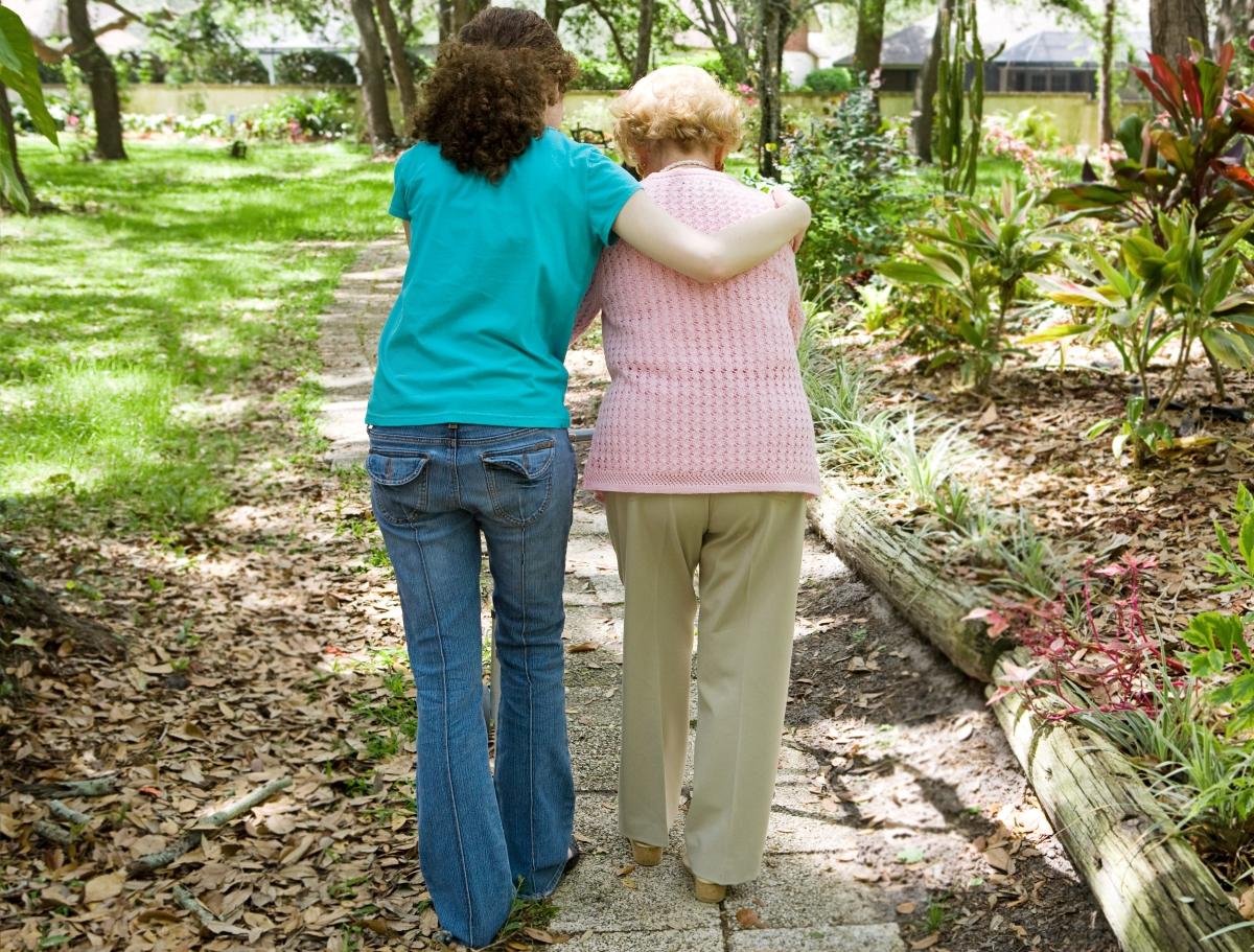 歩行不安定な高齢女性と寄り添って歩く女性の写真