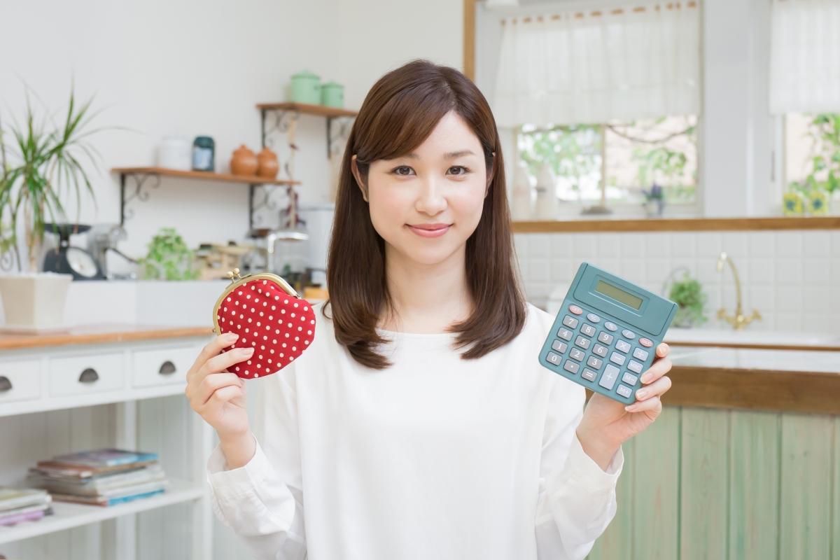 財布と電卓をもつ女性の写真