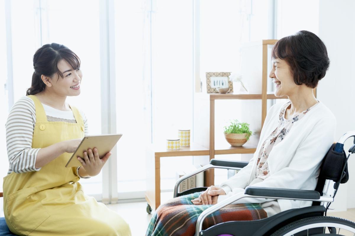 一人暮らしの高齢女性と自宅に訪問するヘルパーの写真