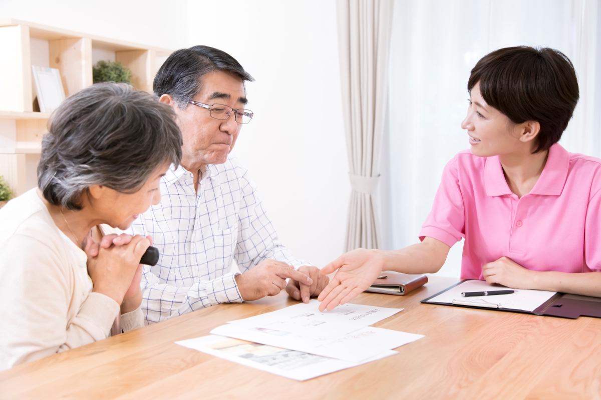 介護保険サービスを申請する老夫婦と職員