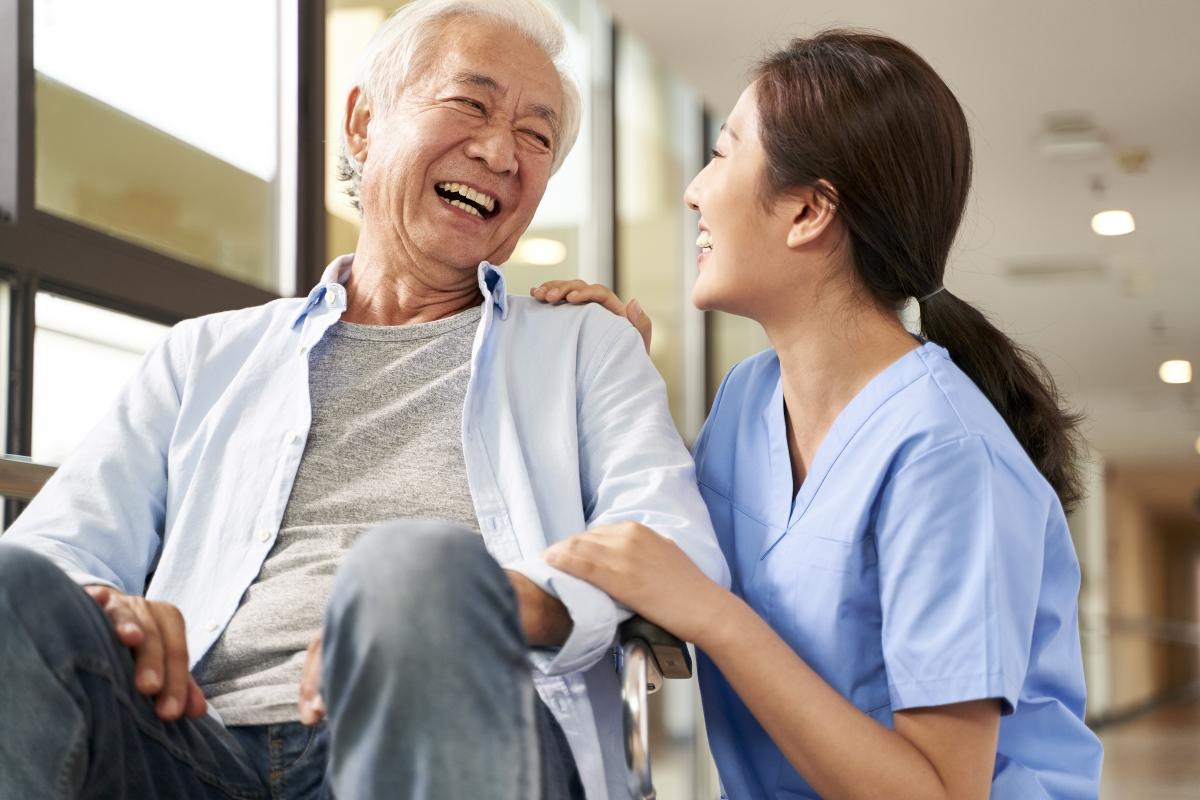 笑顔の高齢男性と介護スタッフの写真