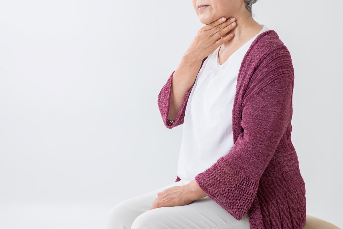 誤嚥する高齢女性の写真