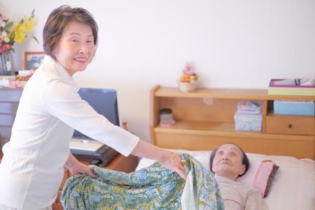 高齢女性に布団をかける自宅介護の写真