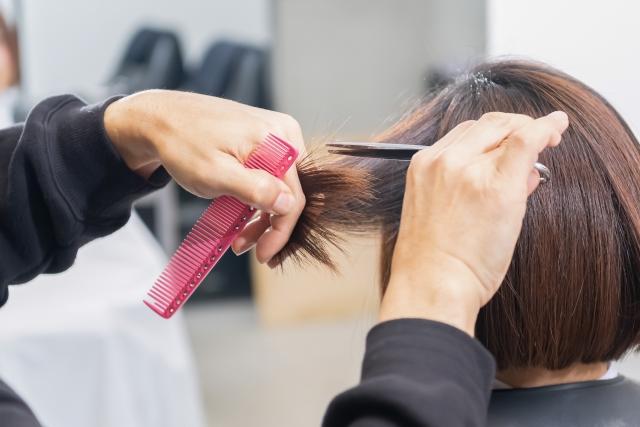 髪をカットする訪問美容師の手元