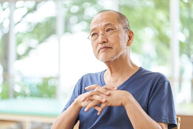 特徴のある顔つきをする認知症高齢男性の写真